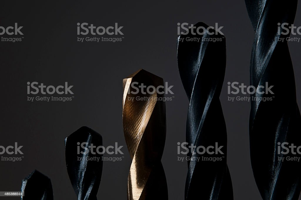 Golden and Black Drill Bits on dark background stock photo