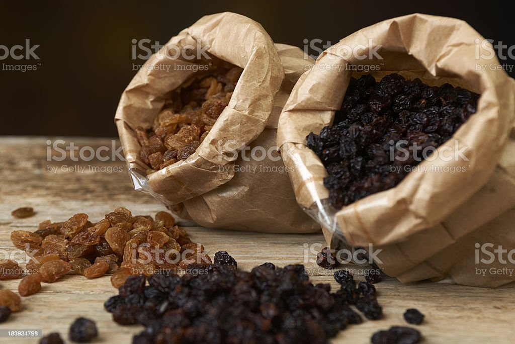 Golden and black raisins in paper bags stock photo