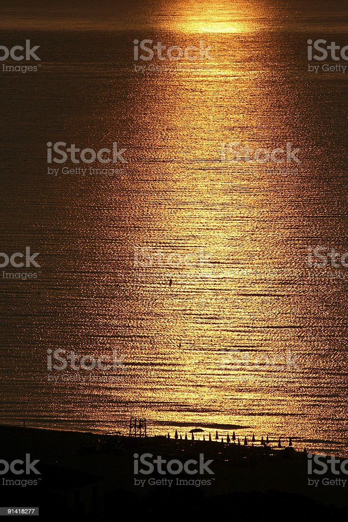 Golden and bronze sea with beach umbrellas silhouettes royalty-free stock photo