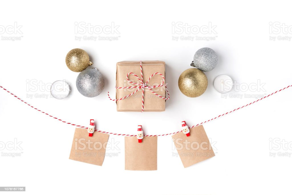 Golden and silver balls, gift, candles, notes with wish on clothespins, Top view White Background Christmas New Year stock photo