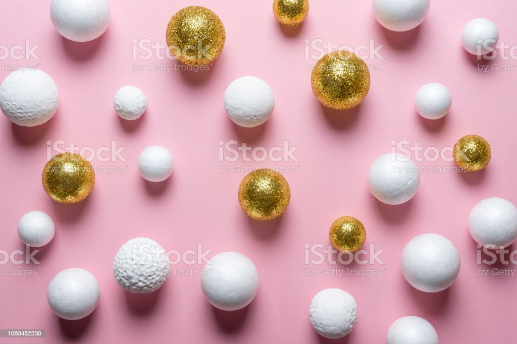 Golden and white glitter ball decoration on pink background. New Year...