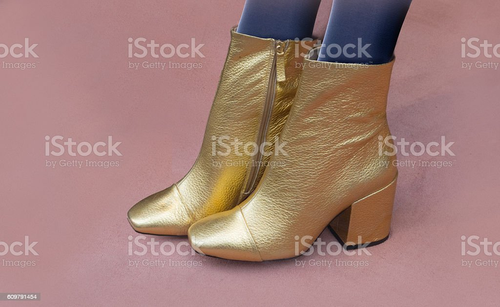 Golden ankle boots with chunky heels and zipper stock photo