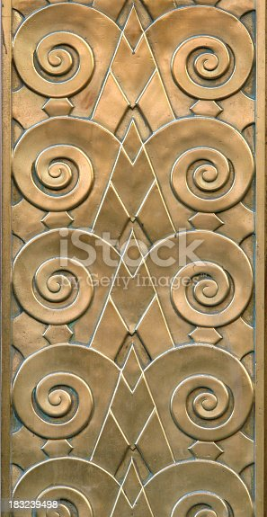 Detail of an Art Deco style bronze relief. The photo was taken in New york City and features a repeating pattern juxaposing strong rising diagonal elements with spiral curlicues suggesting rams horns. The bronze has a rich array of golden hues and is embued with a patination conducive to a structure built in 1929. (See more in the