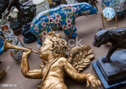 istock Golden baby angel playing on trumpet. Flea market in Paris. 453079715