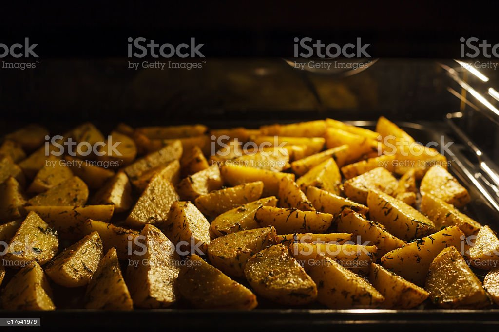 golden baked potato with dill on a metal baking sheet stock photo