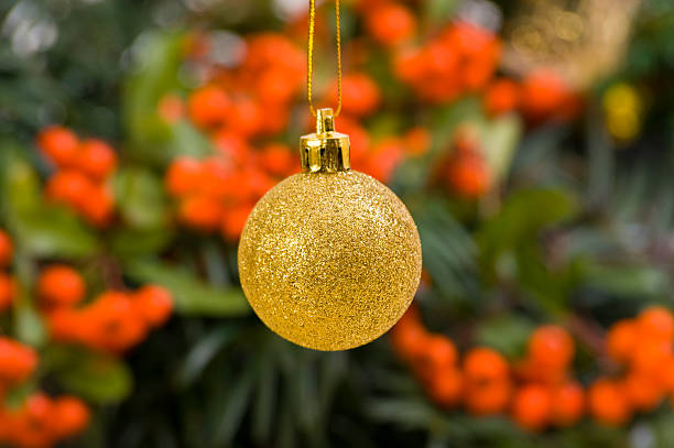 Golden Bauble in Front of Christmas Decoration stock photo