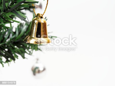 Golden bell hanged on green christmas pine tree branch isolated on white background used for decoration in Christmas and New Year event