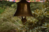 A golden bell hangs in front of a landscape of green plants in the botanical garden in Edinburgh