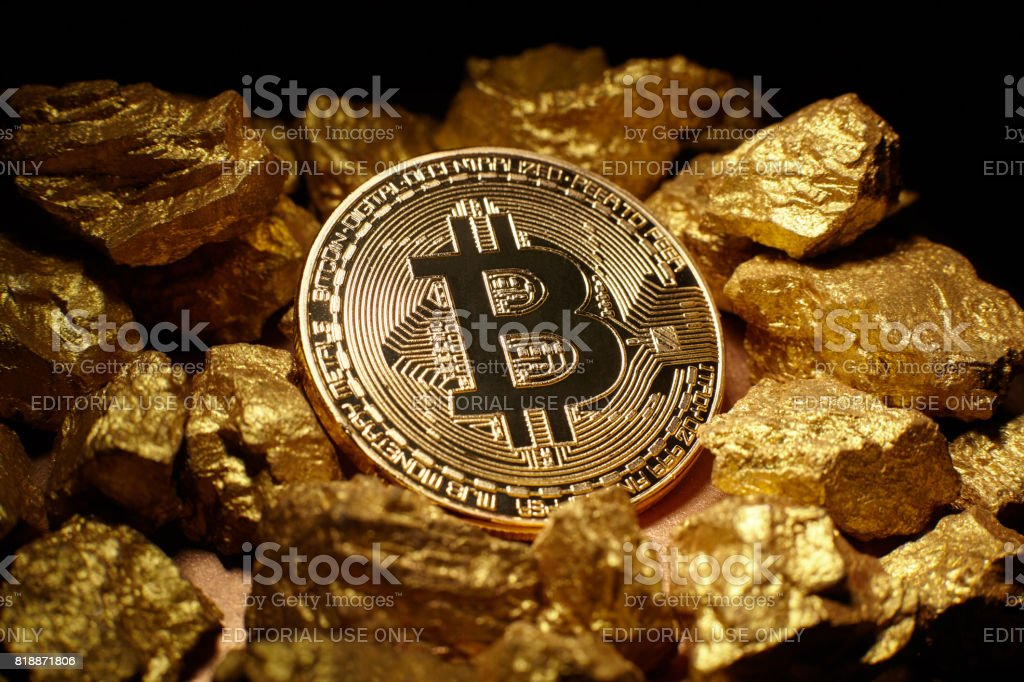 Golden Bitcoin Coin and mound of gold stock photo