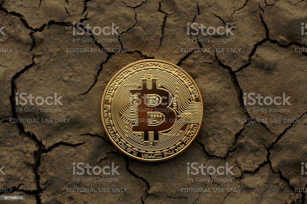 Golden Bitcoin Coin on cracked ground stock photo