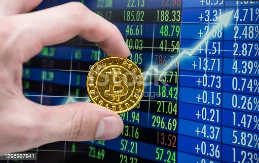 a golden bitcoin coin in front of a stock exchange chart