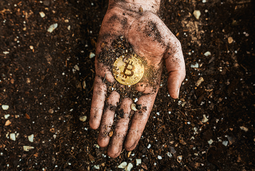 Valencia, Spain, April 5th 2021: A golden bitcoin on the dirty hand of a miner. Metaphor of mining BTC and cryptocurrencies. Digital business and decentralized finances concept.