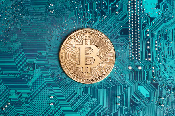 Golden bitcoin replica on computer circuit board stock photo
