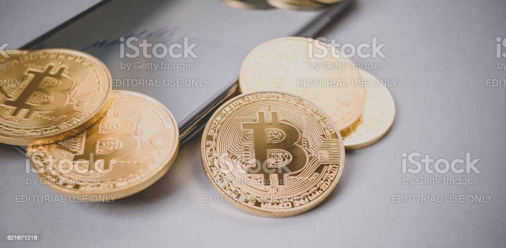Golden Bitcoins placed on smartphone stock photo