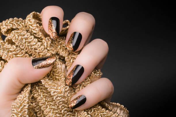 goldene schwarze nägel - gelnägel stock-fotos und bilder