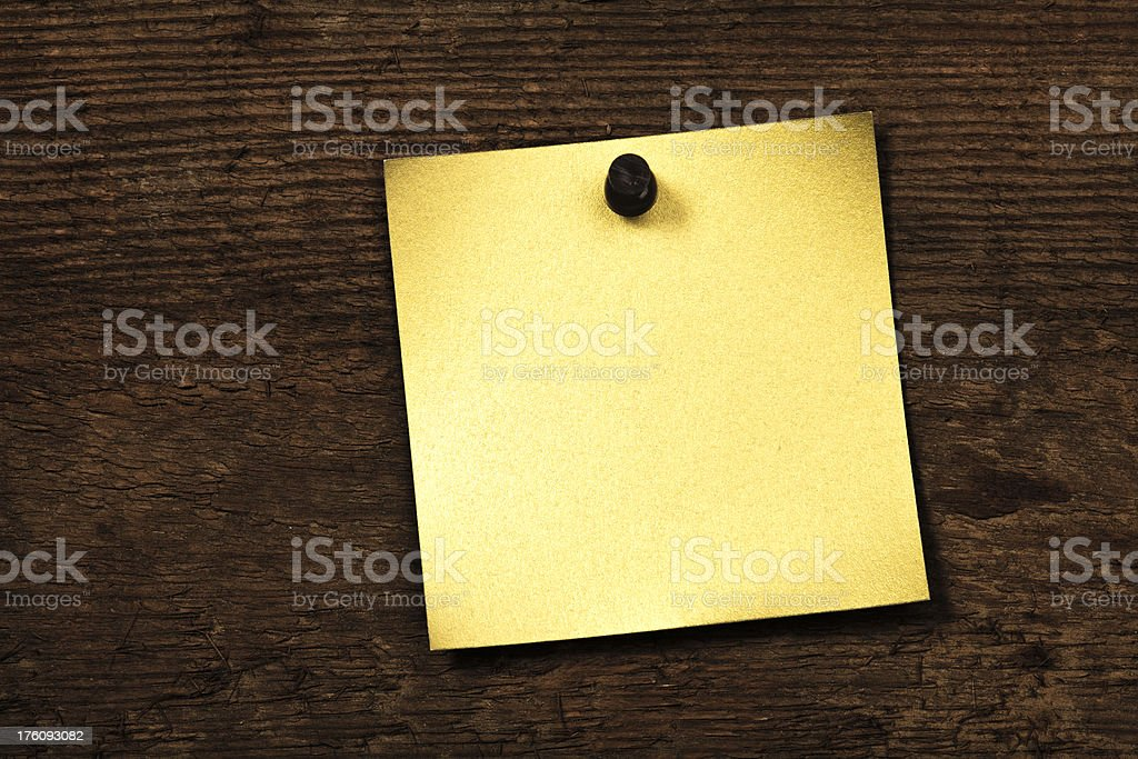 Golden blank note nailed to wood background. royalty-free stock photo