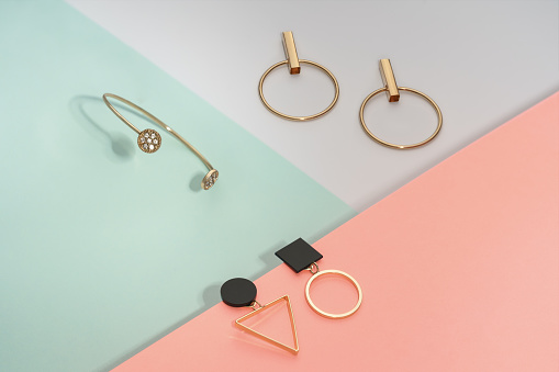 istock Golden bracelet and two golden geometric earrings pairs on pastel colors background pink and blue 1185747571