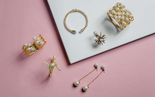 golden bracelets and earrings on pink and white background
