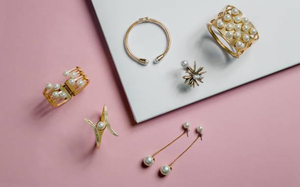 złote bransoletki i kolczyki z perłami na różowym i białym tle - akcesorium osobiste zdjęcia i obrazy z banku zdjęć