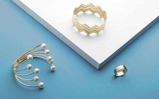 istock Golden bracelets and golden ring on white and blue background - Zigzag bracelet and pearl golden bracelet 1080783708