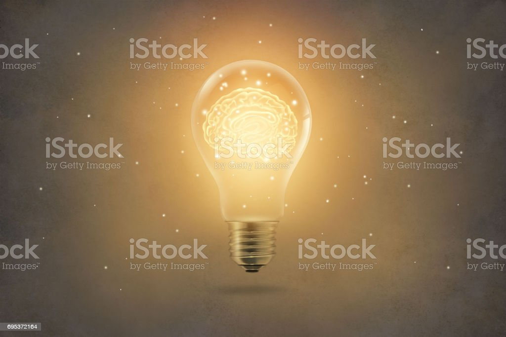 golden brain glowing inside of light bulb on paper texture background stock photo