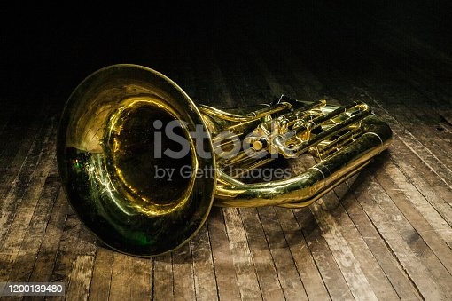istock golden brass instrument tuba lies on a brown wooden stage in the light of the spotlight 1200139480