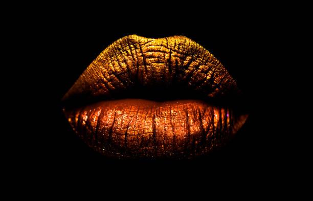 Gyllene brun läppstift på läpparna isolerad på svart bakgrund. Sexiga läppar, kvinnliga mun. Imprint läppar. Lyx cosmetics för flickor och kvinnor. Vackra kvinnliga läppar. Kvinnlig skönhet konceptet flicka bildbanksfoto