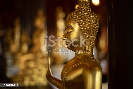 Golden Buddha as bubble bokeh as background, Golden Buddha statue at Wat Krathum Suea Pla temple is public place and famous landmark tourist attraction in Thailand