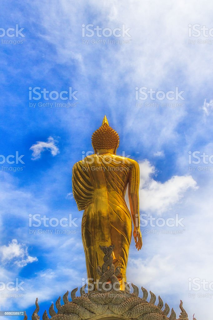 Golden Buddha Statue and blue sky in thai temple stock photo