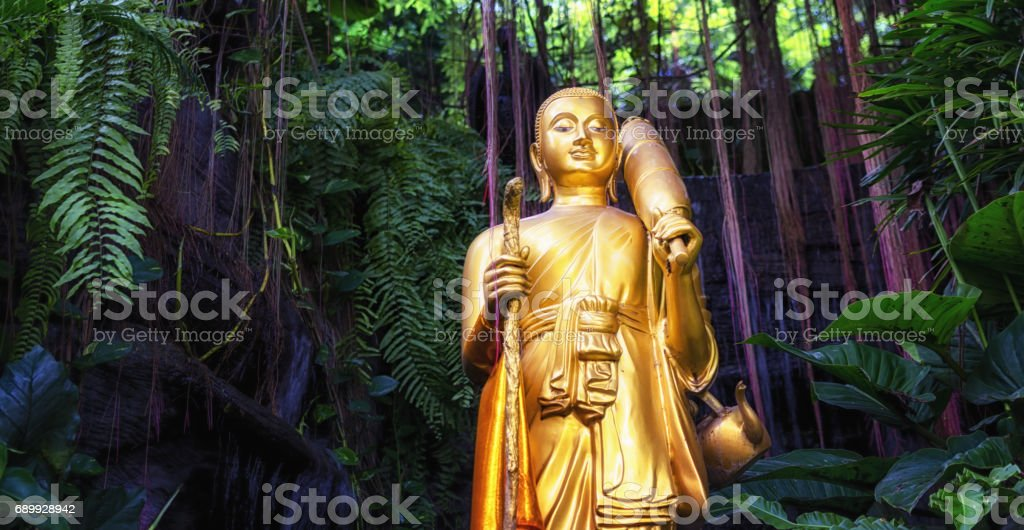 Golden Buddha statue and small artificial waterfall at the Golden Mount at Wat Saket in Bangkok, Thailand. stock photo