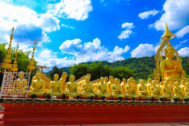 golden buddha statue with among small 1,250 buddha statue at makha bucha buddhist memorial park located at nakhon nayok province, thailand - makha bucha stock photos and pictures