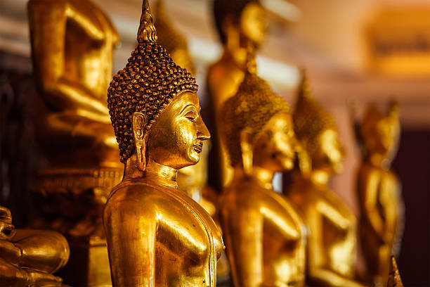 Golden Buddha statues in buddhist temple stock photo