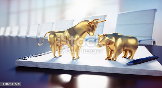 Golden Bull and Bear standing on a Notebook in an sunny Office Room