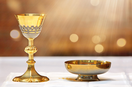 Golden chalice on the altar and rays of light from heaven with empty place for text