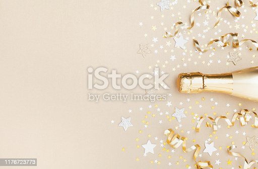 Golden champagne bottle with confetti stars and party streamers top view. Christmas, birthday or wedding background. Flat lay style.