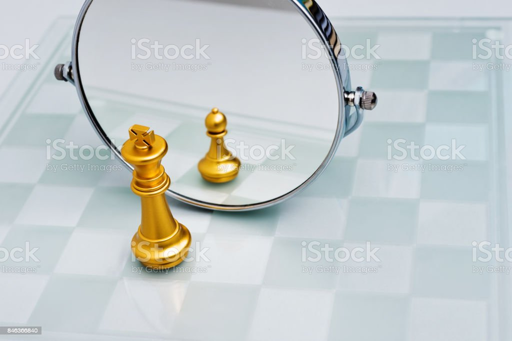 Golden chess king imagining itself as a pawn stock photo