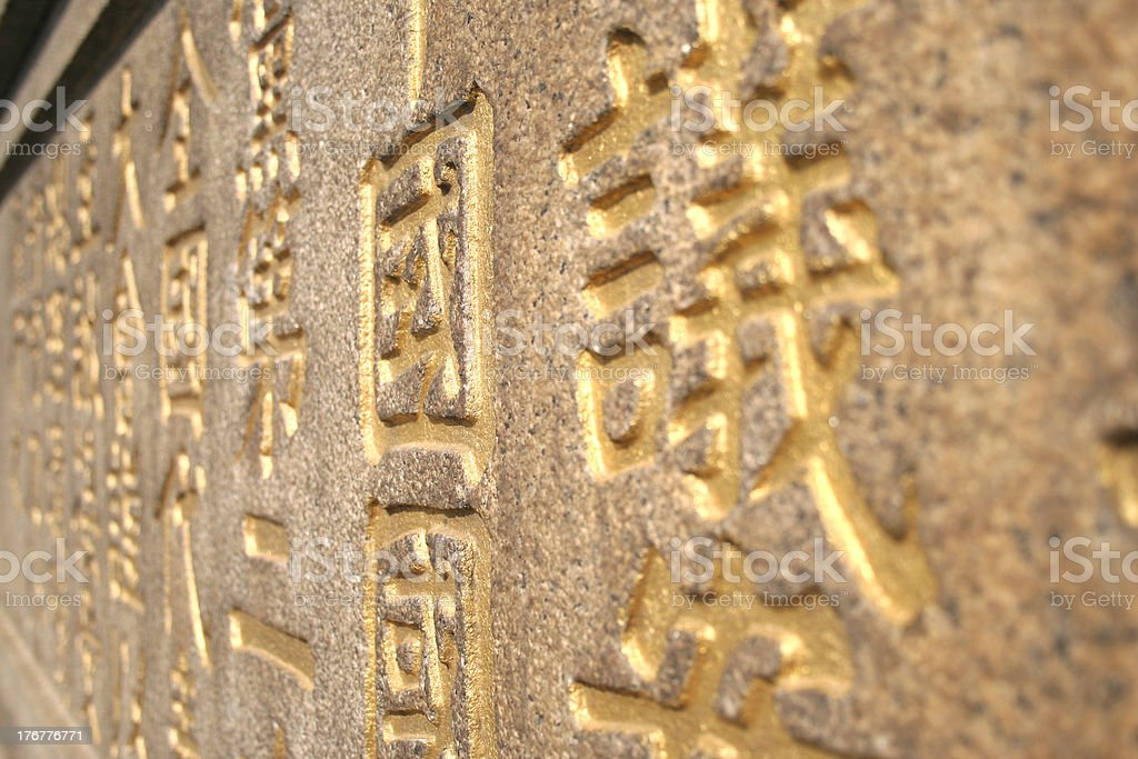 Golden Chinese Characters Carved on Stone Wall royalty-free stock photo