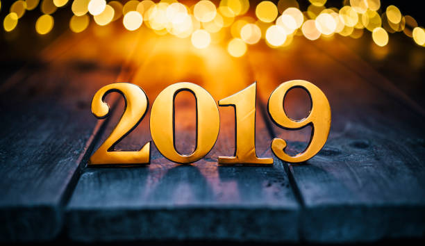 Golden Christmas 2019 - Gold Metal Lights Wood New Year Golden numbers 2019 on old wood and defocused Christmas lights. 2019 stock pictures, royalty-free photos & images