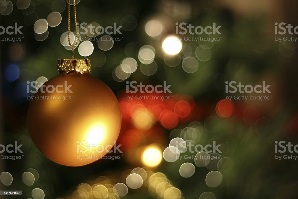 Golden Christmas ball with Christmas tree in the background royalty-free stock photo