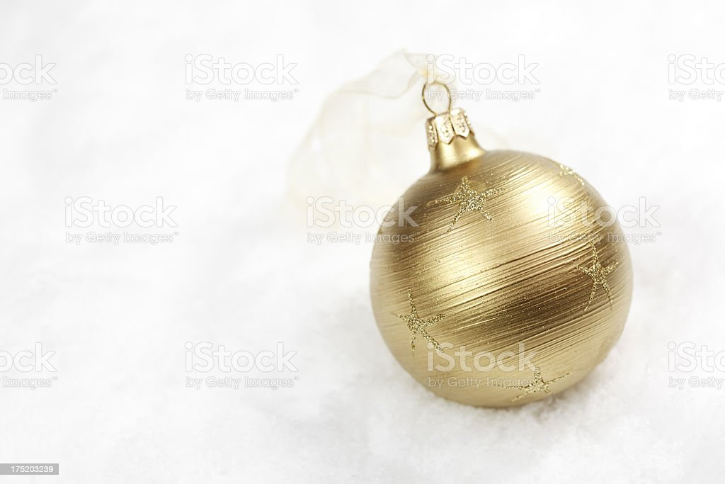Golden Christmas bauble on white snow royalty-free stock photo