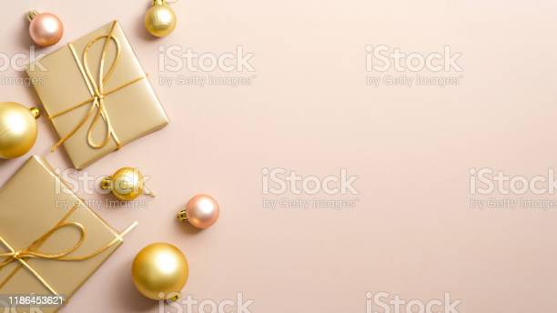 Golden christmas gifts and balls on pastel beige background with copy picture id1186453621?b=1&k=6&m=1186453621&s=612x612&h=qxajzwlsyxhjhbjr 0ezjmm6qnhcslwraymb3gpbslc=