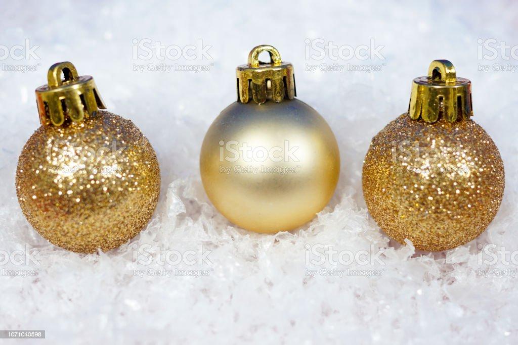 3 golden christmas glitter balls on snow