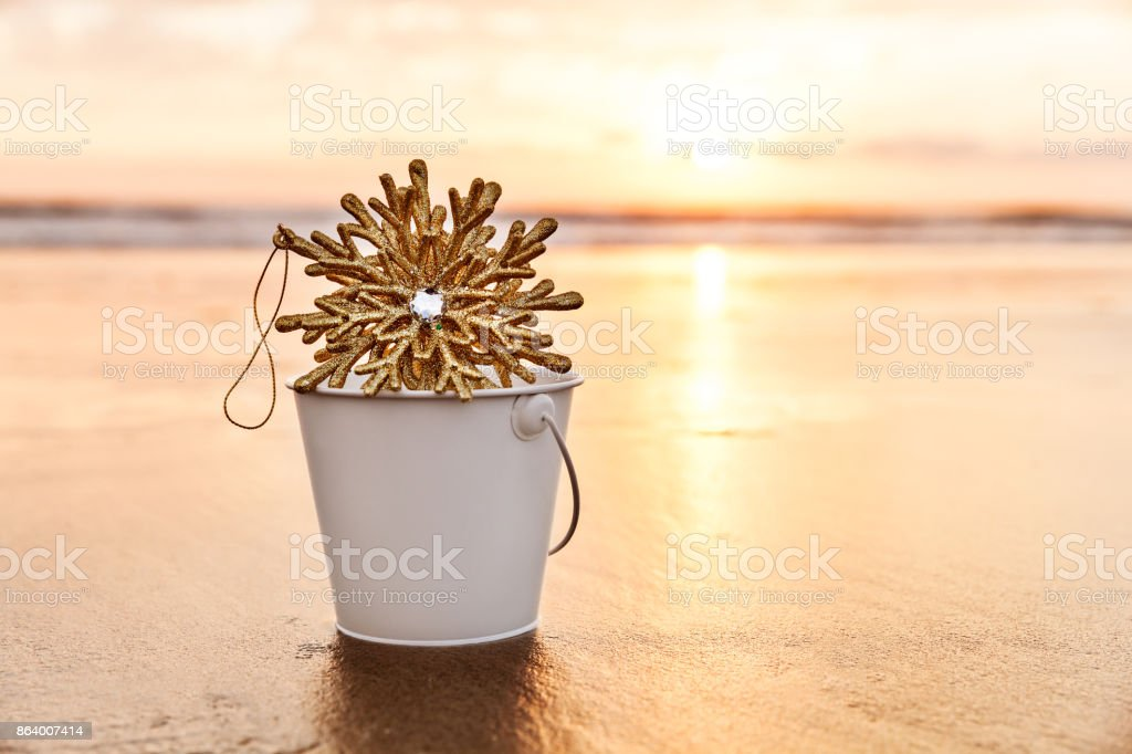 Golden Christmas Snowflake Collected in a White Bucket at Sunset on the background of Beach and Sea stock photo