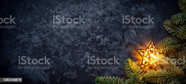 Photo of Golden Christmas star on dark metal - Holiday Background Fir Tree Branch