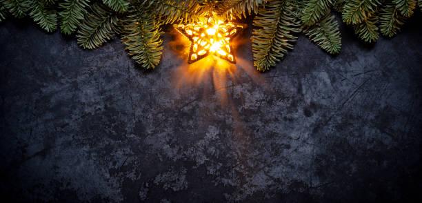Golden Christmas star on dark metal - Holiday Background Fir Tree Branch stock photo