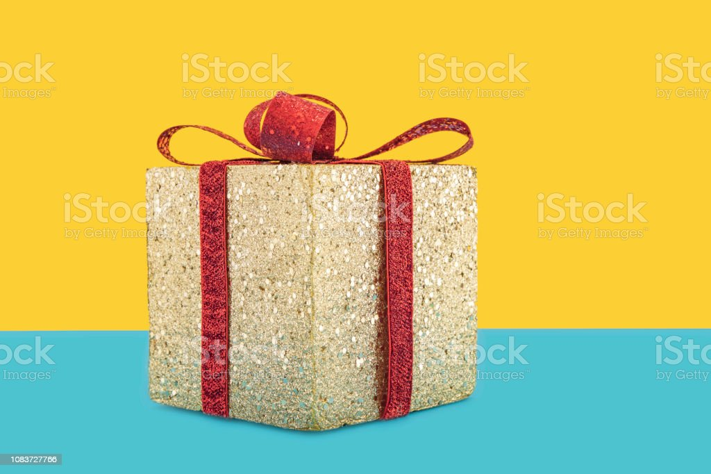 Golden christnas box with red ribbon and bow.