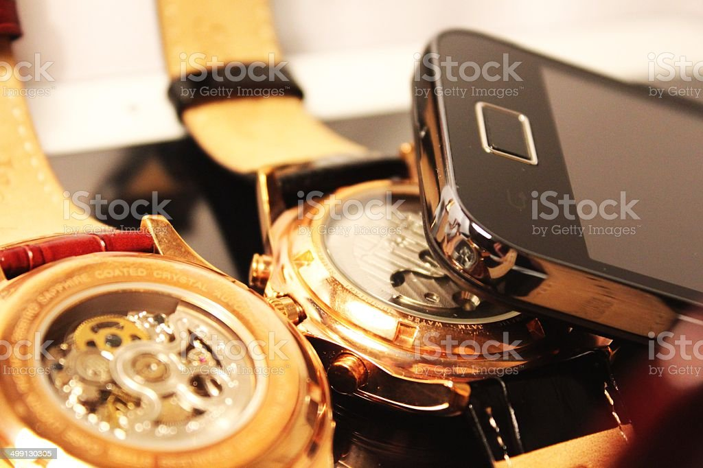 Golden chronometers and black cell phone royalty-free stock photo