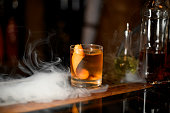 istock Golden cocktail in the glass with one ice cube and orange zest in the smoke 1162724950
