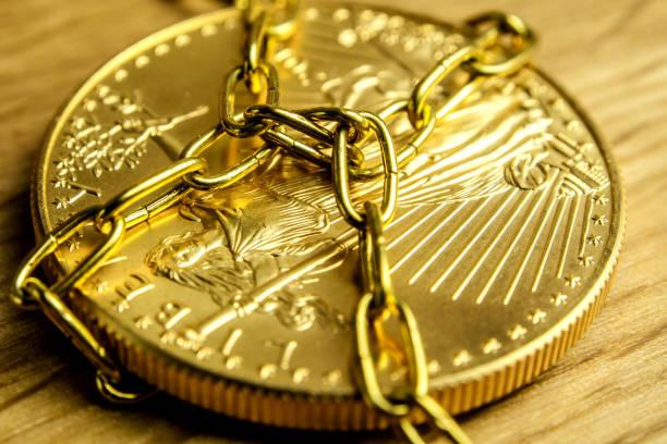 goldene münze in goldenen ketten gehalten, während der verlegung auf hölzernen hintergrund, goldpreis manipulation konzept - aurum stock-fotos und bilder