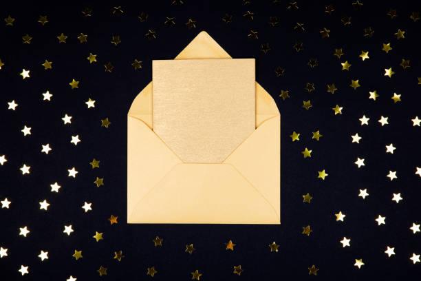 Goldene (gelbe) farbige, leere Karte in geöffneter Hülle auf schwarzem Hintergrund, die mit Sternkonfetti verziert ist. – Foto